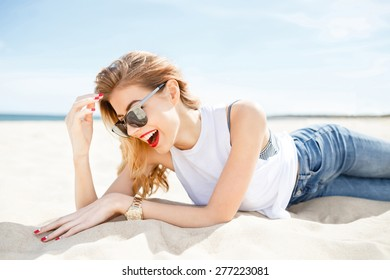 Attractive girl in sunglasses posing lying on the sea beach on a sunny day on the background of the sea and clear sky.