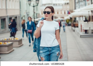 Attractive girl in sunglasses walking along the street. White t-shirt. Mock-up.