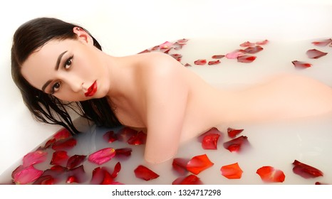 Attractive girl takes a bath with milk and rose petals
