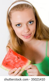 an attractive girl takes bite of watermelon