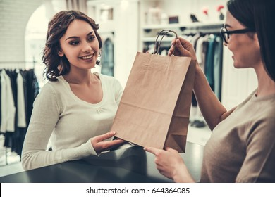 Attractive girl is taking shopping bags with the purchases, talking with shop assistant and smiling while doing shopping in boutique