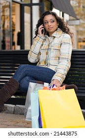 An attractive girl talking on her cell phone while out shopping in the city.