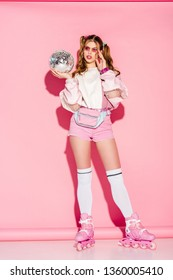 attractive girl touching sunglasses and holding shiny disco ball while standing in roller-skates on pink