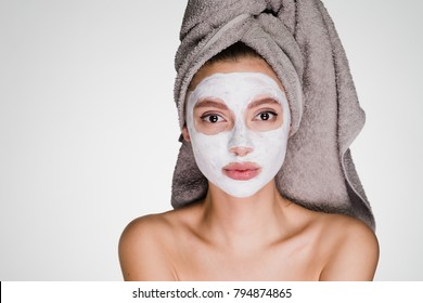 an attractive girl with a towel on her head applied a white moisturizing face mask
