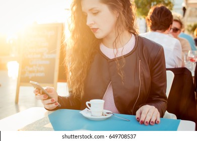Attractive girl using smartphone at restaurant drinking coffee sunny outdoors background