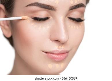 Attractive girl using tassel for concealer
