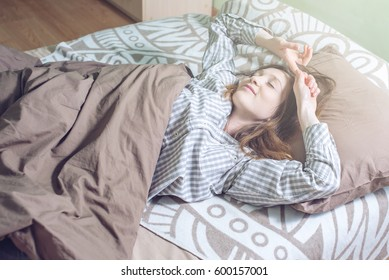 Attractive girl waking up early in the morning, lying sleepy in bed and nice with a smile stretching