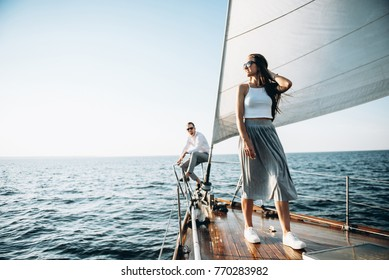 An attractive girl walks on a wooden yacht. She swims with her handsome guy on the sea