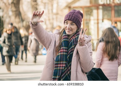 The attractive girl walks in the winter. On her a violet cap, a pink jacket and a dark checkered scarf. She takes the improvised selfie by means of a hand and smiles. The girl shows a peace sign.