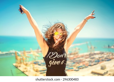 Attractive girl wearing black tank top smiling, laughing and taking pictures with camera phone. Traveling concept with happy woman. Soft colorful effect on photo