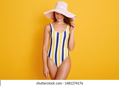 Attractive girl wearing striped swimsuit and hat, loking downand keeps one hand on her hat, posing isolated over bright yellow background, has perfect body and healthy skin. Vacation concept.