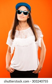 Attractive girl, wearing in white blouse, cap and blue sunglasses, is posing on orange background, waist up