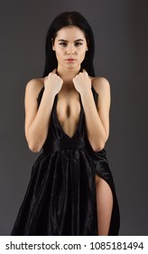 Attractive girl wears expensive fashionable evening dress with erotic slit. Sexy decollete concept. Woman in elegant black evening dress with decollete, dark background. Lady, sexy girl in dress.