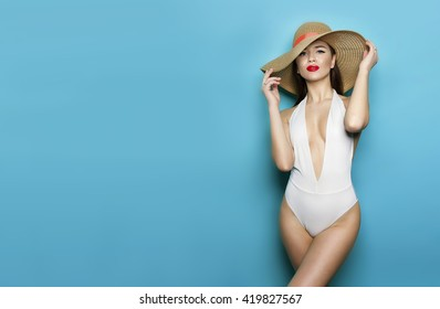 attractive girl in a white bathing suit on a blue background with a perfect body and a radiant smile by putting his hands in the side for magazine cover