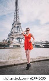 Attractive girl in white dress sending air kiss under Eiffel tower, Paris, France.