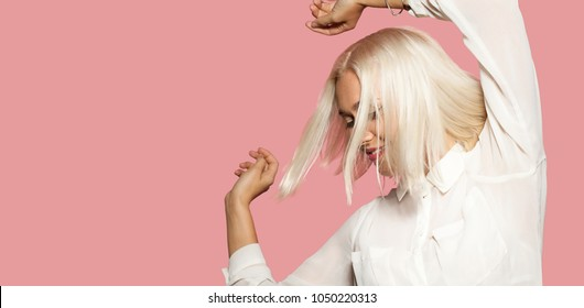 Attractive girl in white shirt dancing. Young woman having fun, pink wall on background. Studio portrait of beautiful blonde hair model. Concept of party and fun.