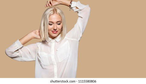 Attractive girl in white shirt dancing. Young woman having fun, beige wall on background. Studio portrait of beautiful blonde hair model. Concept of party and fun.