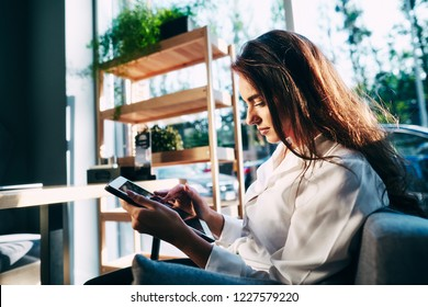 Attractive girl in white shirt working in cafe with gray tablet, online shopping concept, freelance work in progress, work from home.