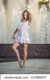 98b7f7e9d3b4 Attractive girl in white short dress sitting in front of a fountain in the  summer hottest