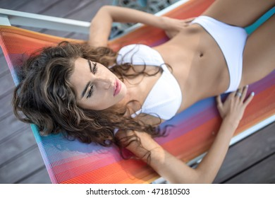 Attractive girl in a white swimsuit lies outdoors on the multi-colored deck chair and looks in front of herself with parted lips. She holds her hands near her hips. Shoot from above. Horizontal.