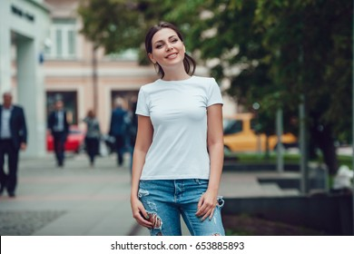Attractive girl in a white T-shirt on the street. Mock-up.