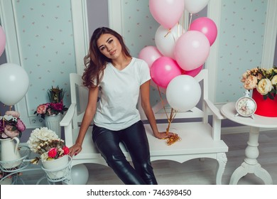 Attractive girl in a white t-shirt sits and holds balloons. Mock-up.