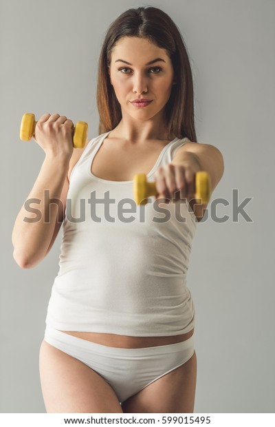 Attractive girl in white underwear is holding dumbbells, looking at camera and smiling, on gray background