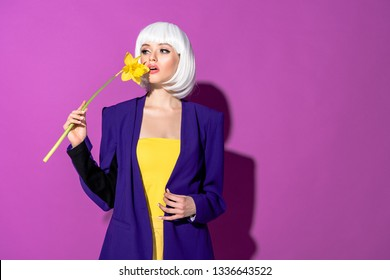 Attractive girl in wig sniffing flower on purple background