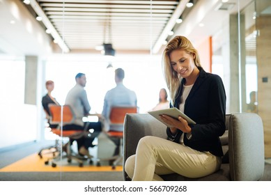 Attractive girl working on a tablet while meeting is in progress.