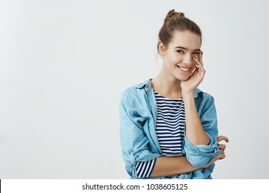 Attractive girlfriend can not stop gazing at boyfriend. Slender caucasian woman with bun hairstyle tenderly touching cheek with palm and smiling cheerfully at camera while standing over gray wall.