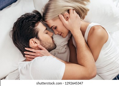 attractive girlfriend and handsome boyfriend laying in bed with closed eyes