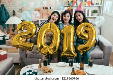 attractive girls celebrating new year eve at home. young friends carrying gold 2019 number balloons cheerfully having fun in house party. asian women indoor lifestyle concept.