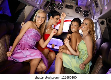 Attractive girls in evening dress having party in limo, smiling.