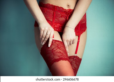 Attractive girl's legs in red lace lingerie stockings