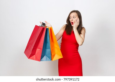 Attractive glamour caucasian fashionable young brown-hair woman in red dress holding multi colored packets with purchases after shopping isolated on white background. Copy space for advertisement