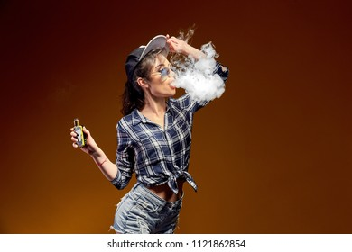 Attractive glamour woman standing and vaping on yellow background.