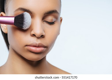 Attractive good looking woman putting on makeup