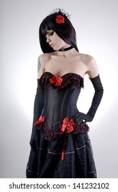 Attractive gothic girl in black and red outfit, studio shot