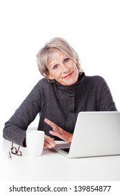 Attractive grey haired senior woman with a laptop shrugging her shoulders and grimacing showing her ignorance of modern technology