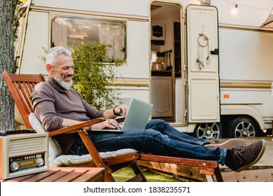 Attractive grey-haired man resting on the wooden deck chair using laptop with caravan van behind - Shutterstock ID 1838235571