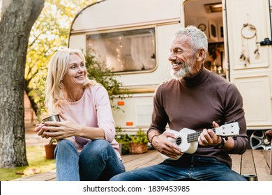 Attractive grey-haired mature man playing the ukulele for his beautiful aged blond wife near the van