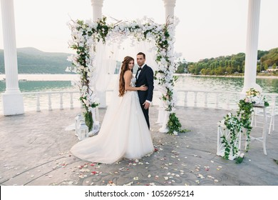 Attractive groom and bride at wedding day ceremory with arch and lake on background stands together. Beautiful newlyweds, young woman in white dress and long hairs, men in black suit. Happy family