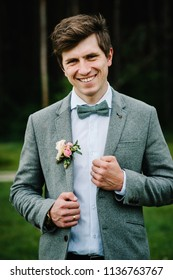 The attractive groom in a suit and bow tie with boutonniere or buttonhole on jacket, is stands on the background greenery in the garden, park. Nature.