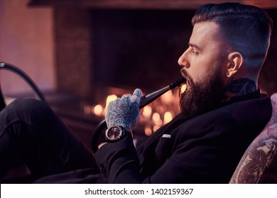 Attractive groomed man is relaxing on lounge near fireplace while smoking hookah. He has tattoo and watch on his hand.