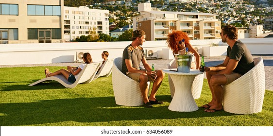 Attractive group of young friends enjoying each others company along with some alcoholic beverages as social lubricant, creating a warm positive atmosphere.