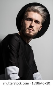 Attractive guy in black clothes with the hat on his head and stylish hairdo. Male model with ashen hair.
