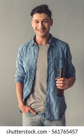 Attractive guy in casual clothes is holding a bottle of beverage, looking at camera and smiling, on gray background