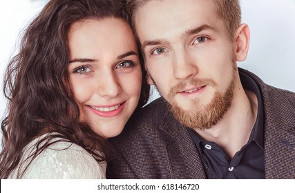 Attractive guy with a girl look at camera in the room