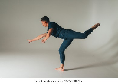 attractive guy in jeans dancing, jumping, shot of mad, crazy, cheerful, successful, lucky guy in casual outfit, jeans, jumping with hands up, triumphant, gesturing against white background