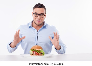 Attractive guy is looking at the hamburger with temptation. He is ready to eat it. The guy is sitting at the table and happily smiling. Isolated on background and copy space in right side